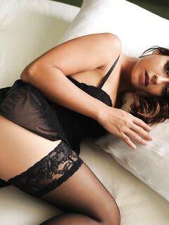 Молодая девица эротично стянула чулки на кровати - фото