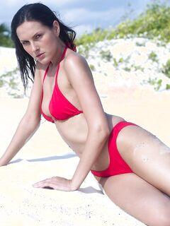 Брюнетка в красном купальнике с голой жопой в песке - фото