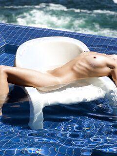 Молодая красавица голая купается в бассейне - фото