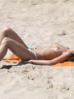 Нудистка загорает на пляже - фото