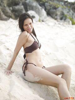 Нудистка лежит на песке без трусов - фото