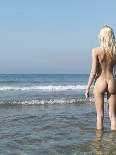 Светловолосая нудистка наслаждается солнцем на пляже - фото