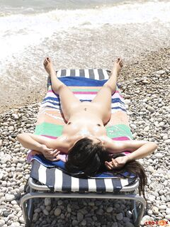 Голая азиатка наслаждается солнышком на пляже - фото