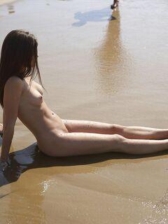 Голая нудистка измазалась песком на пляже - фото