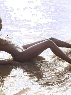 Стройная негритянка голая купается на пляже - фото
