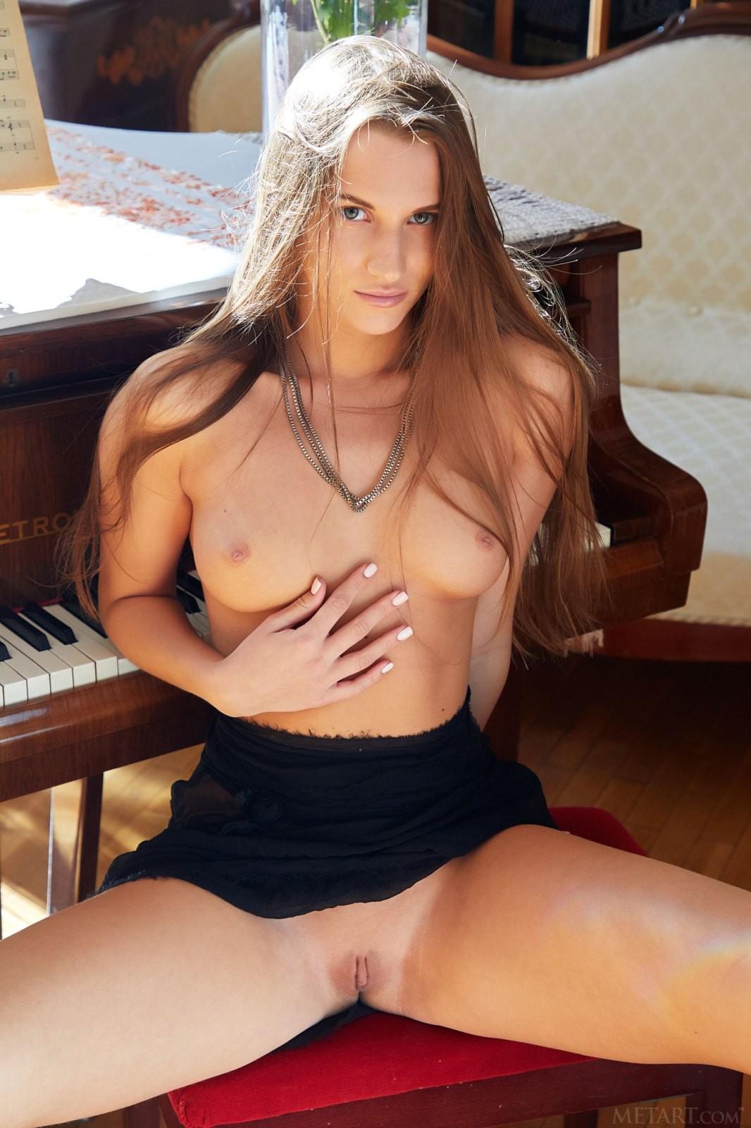 Девушка демонстрирует сочную попку у рояля - фото