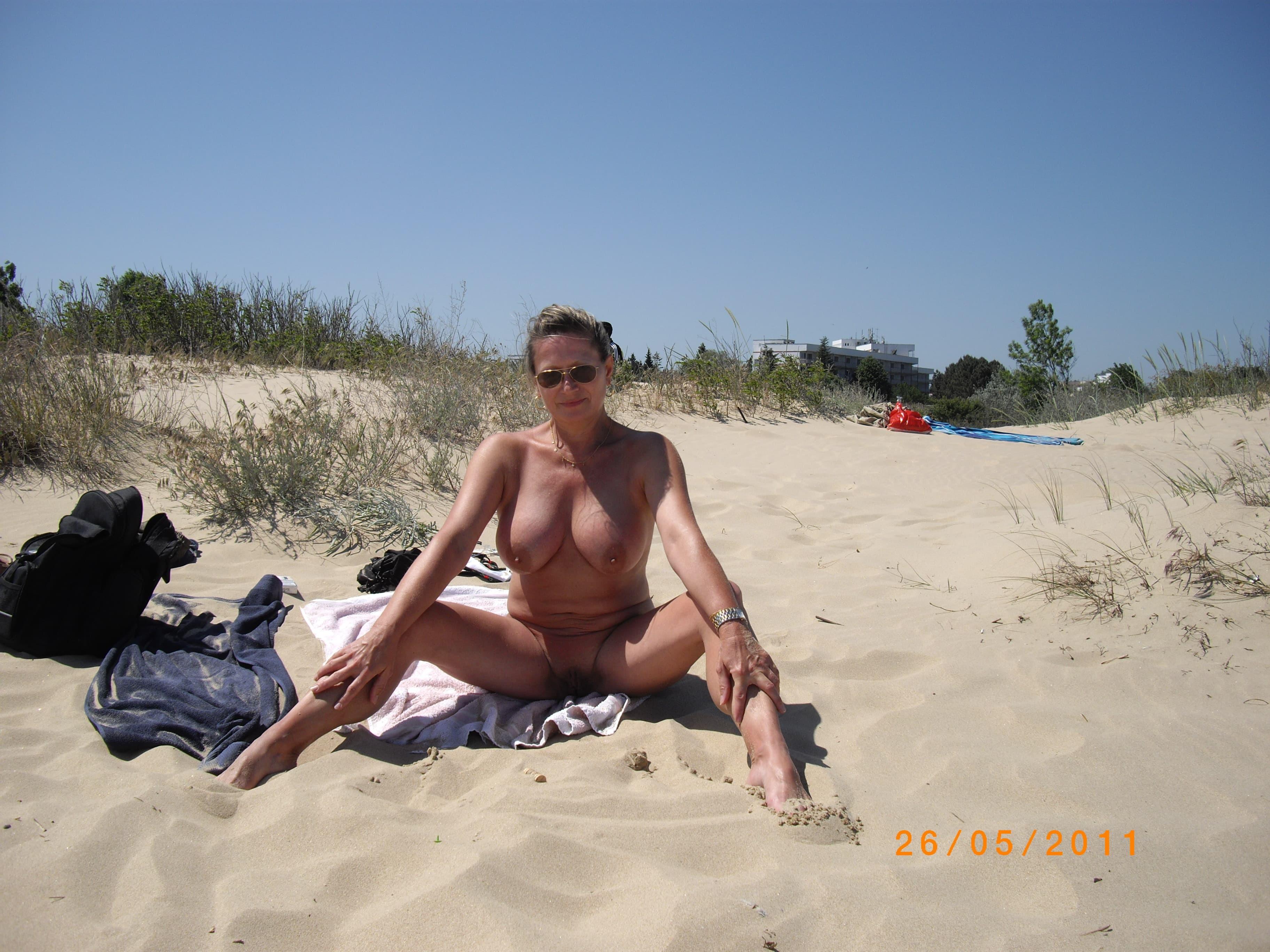Зрелая голая нудистка загорает на пляже - фото