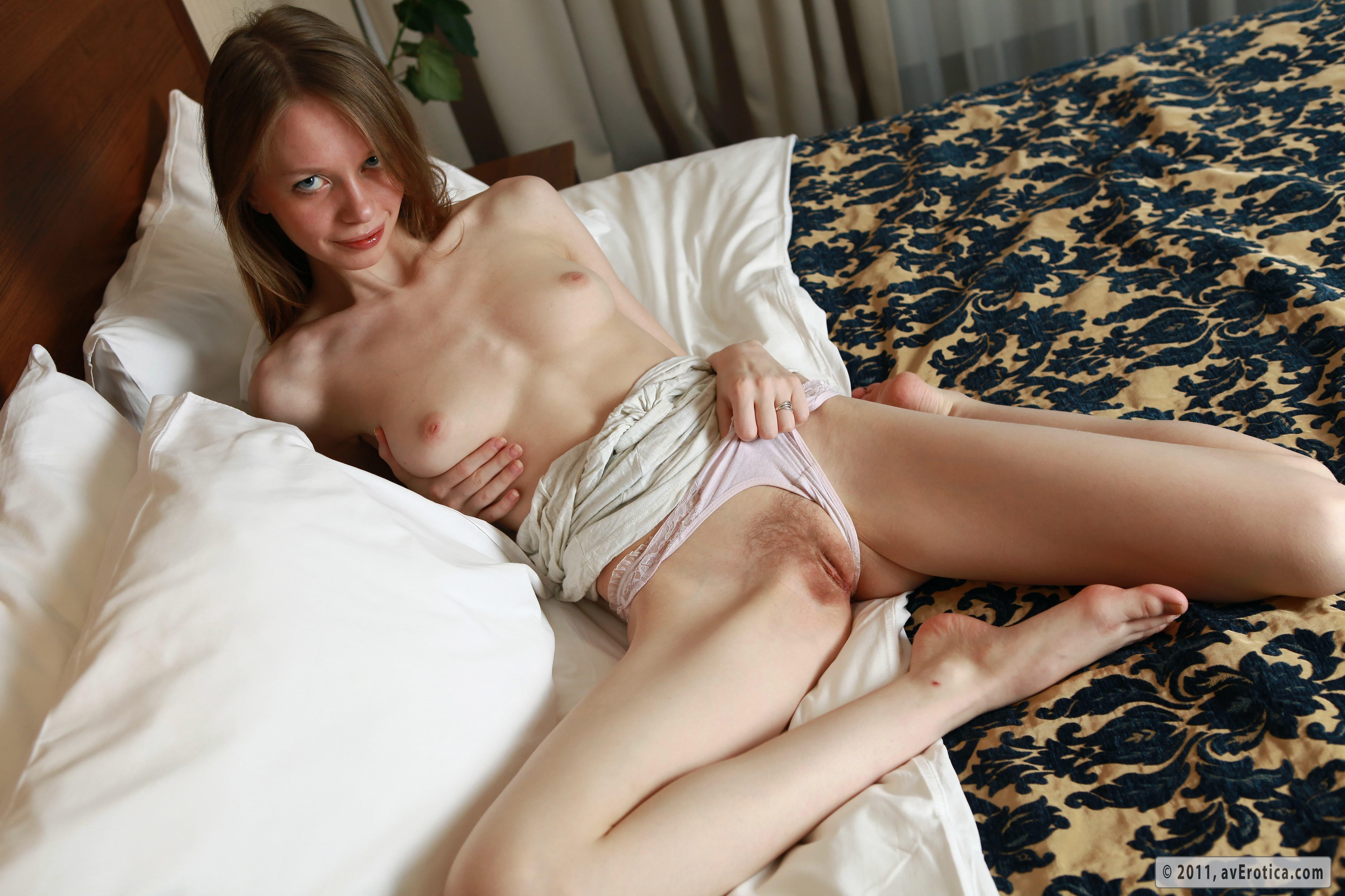 Милашка показывает промежность в постели - фото