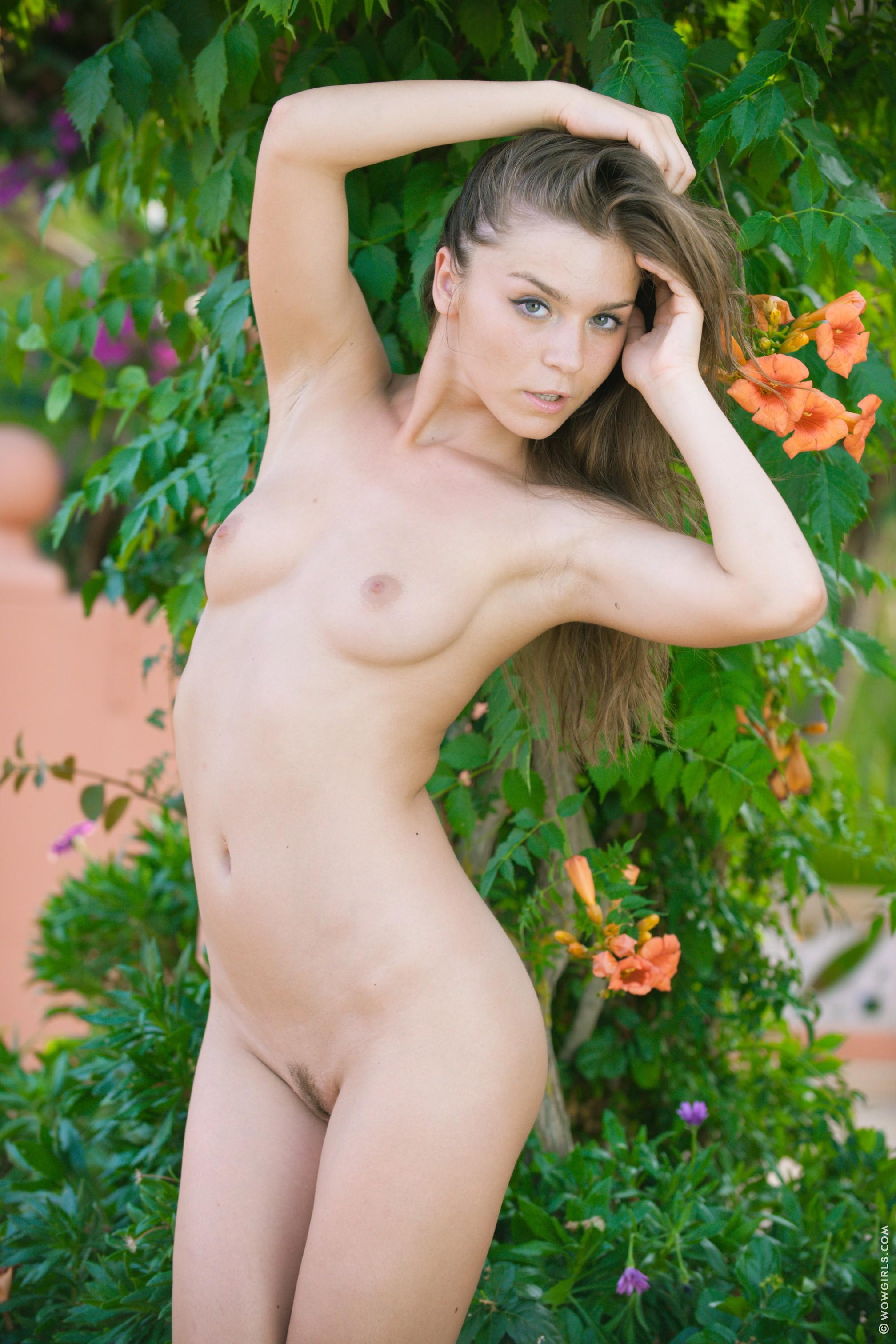Голенькая молодая девица эротично позирует на улице - фото