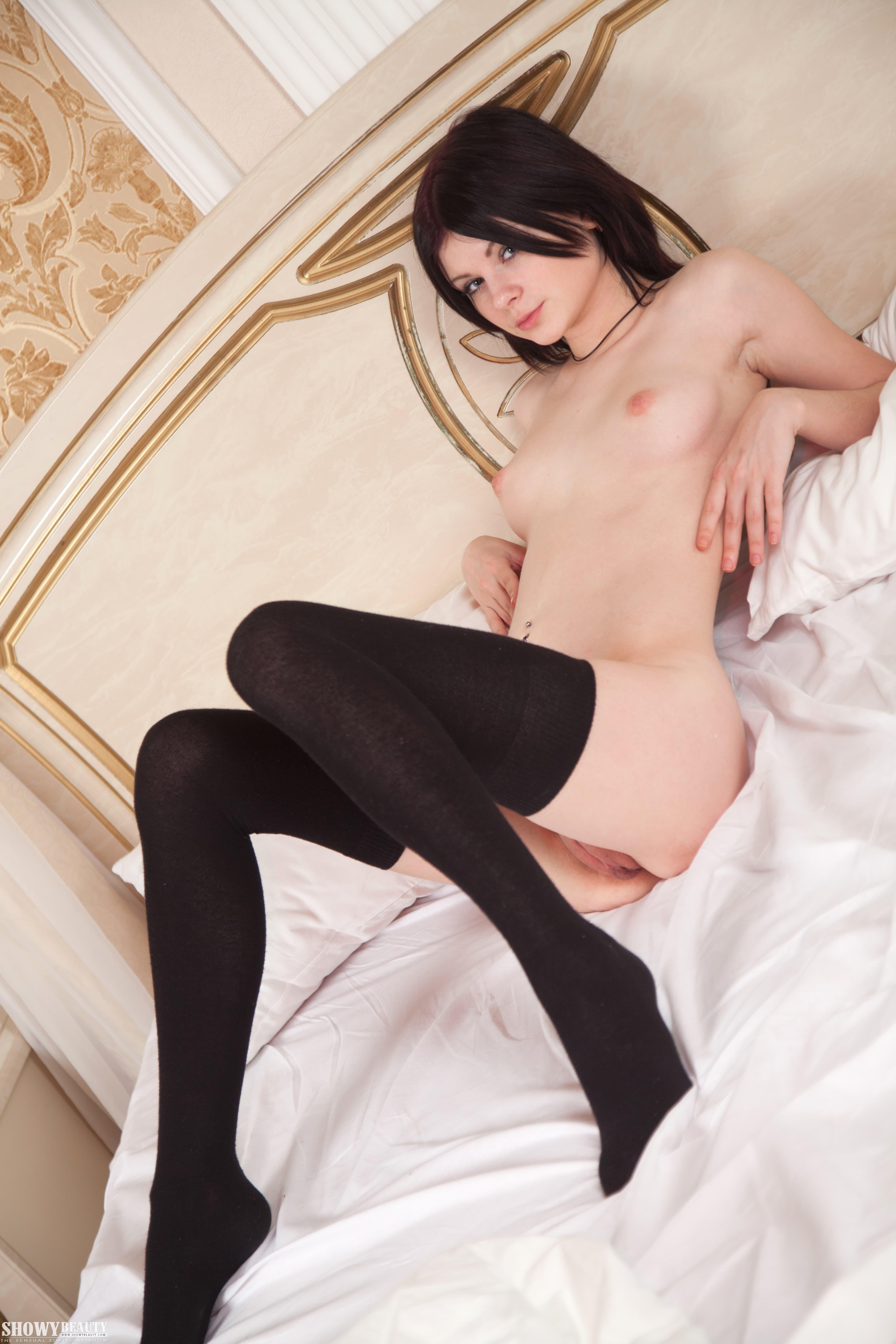 В чулках лежит на спине в постели - фото