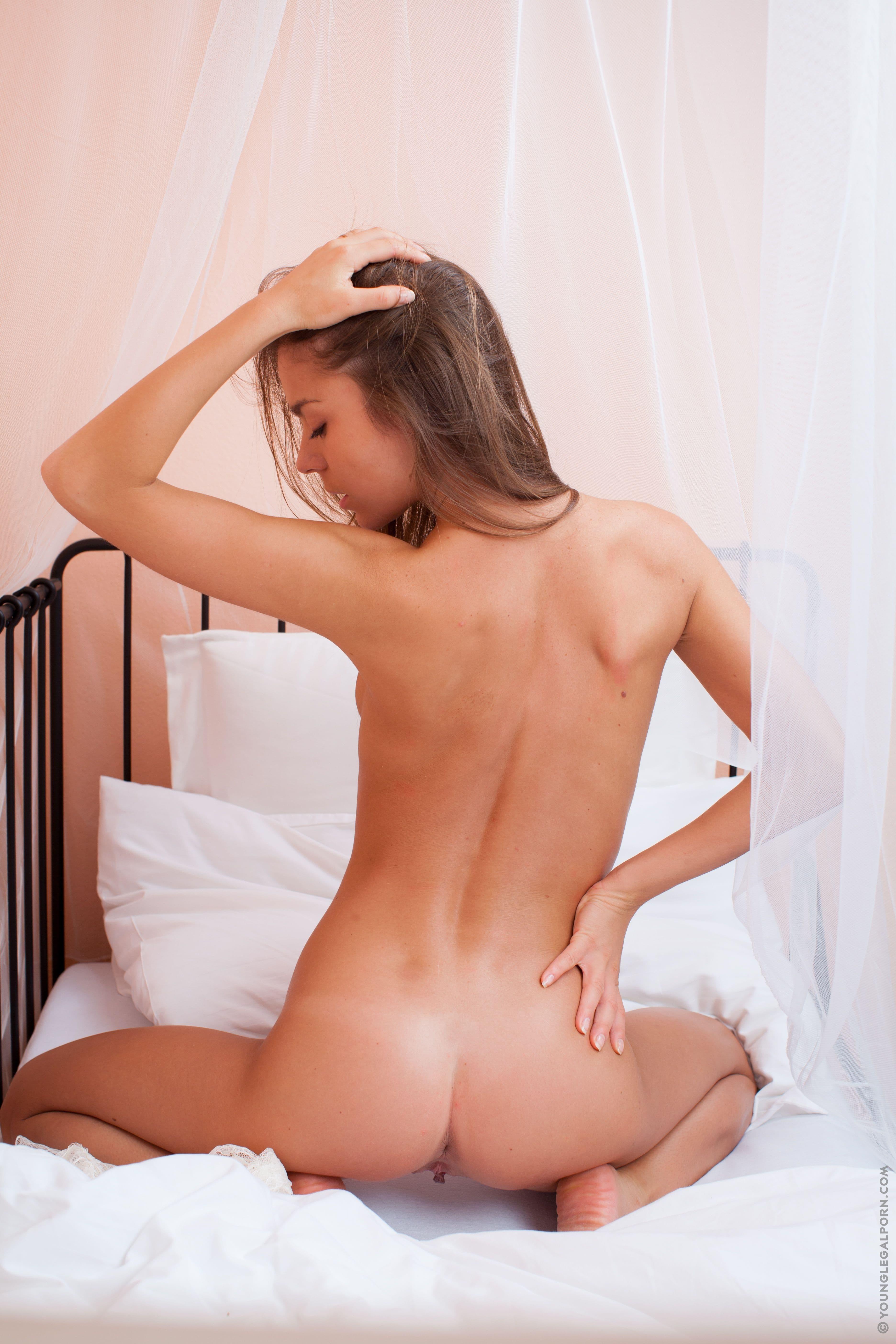 Возбужденная шатенка трогает сиськи на кровати - фото