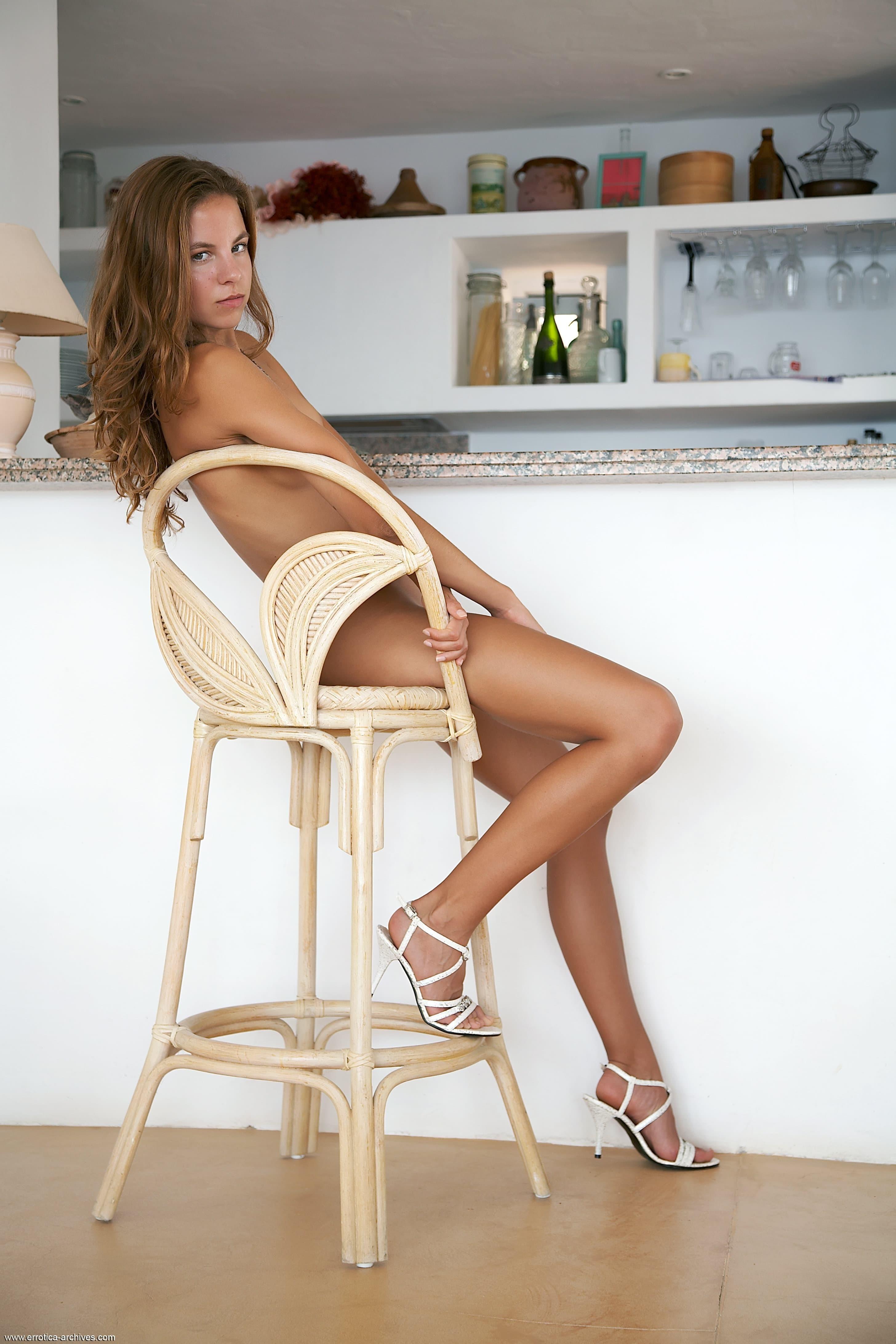 Загорелая голая красавица позирует у барной стойки - фото