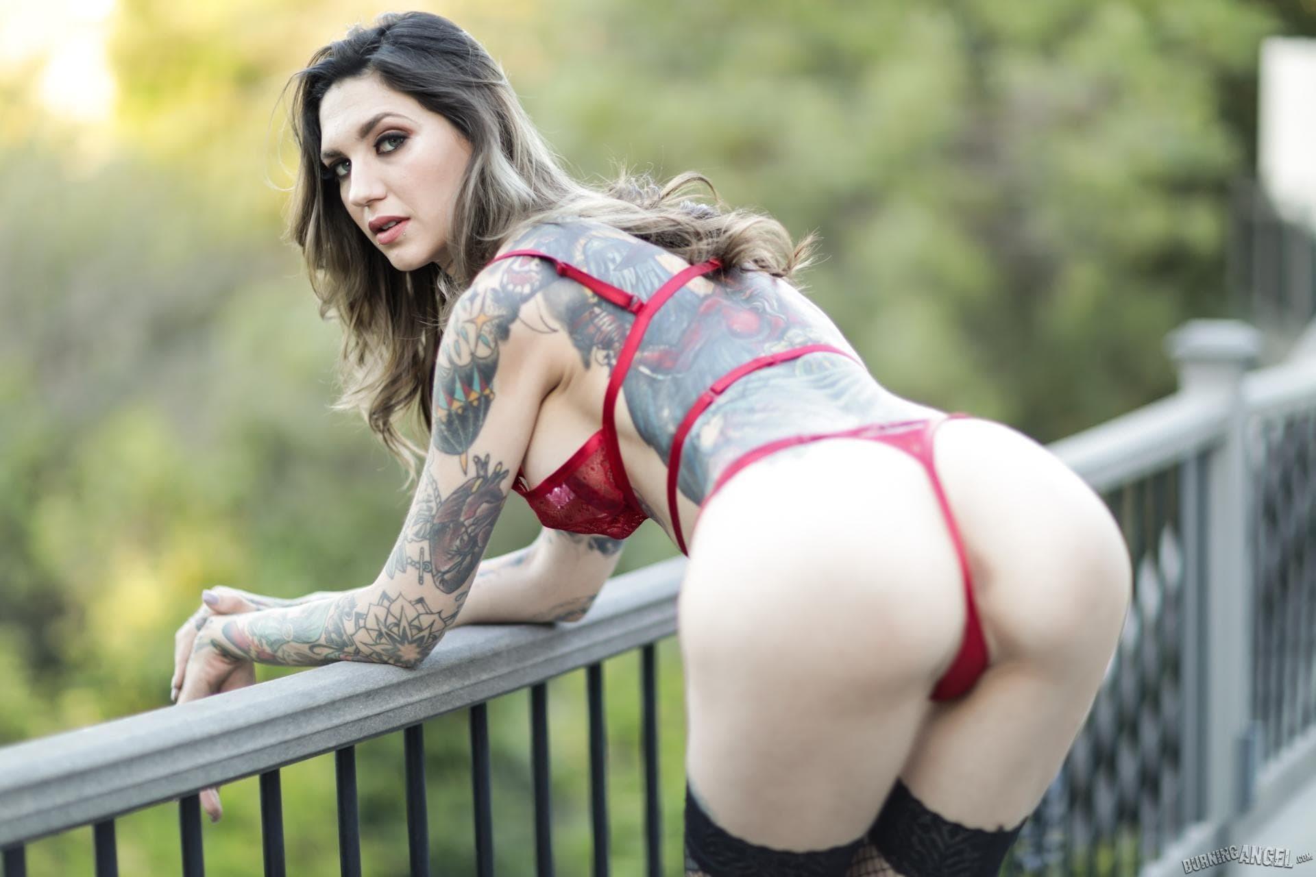 Девушка в татуировках показывает попку на балконе - фото