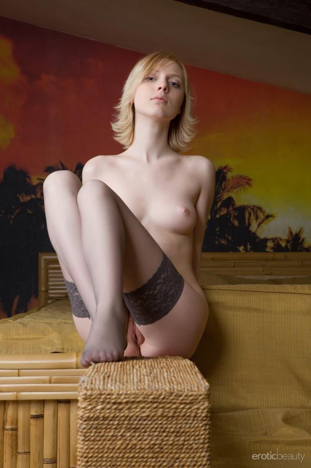 Милая блондинка в чулках красуется в спальне - фото