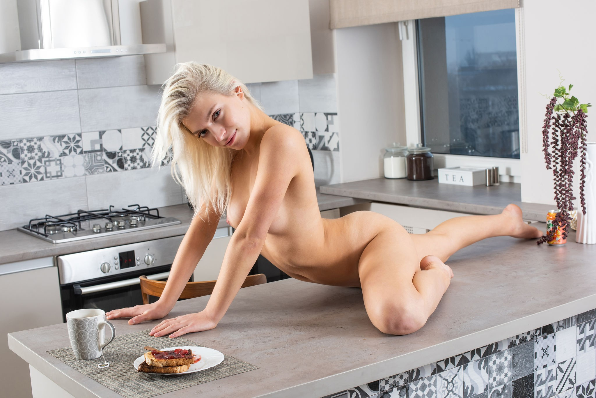 Блондинка с красивой писькой и попой позирует на кухне - фото