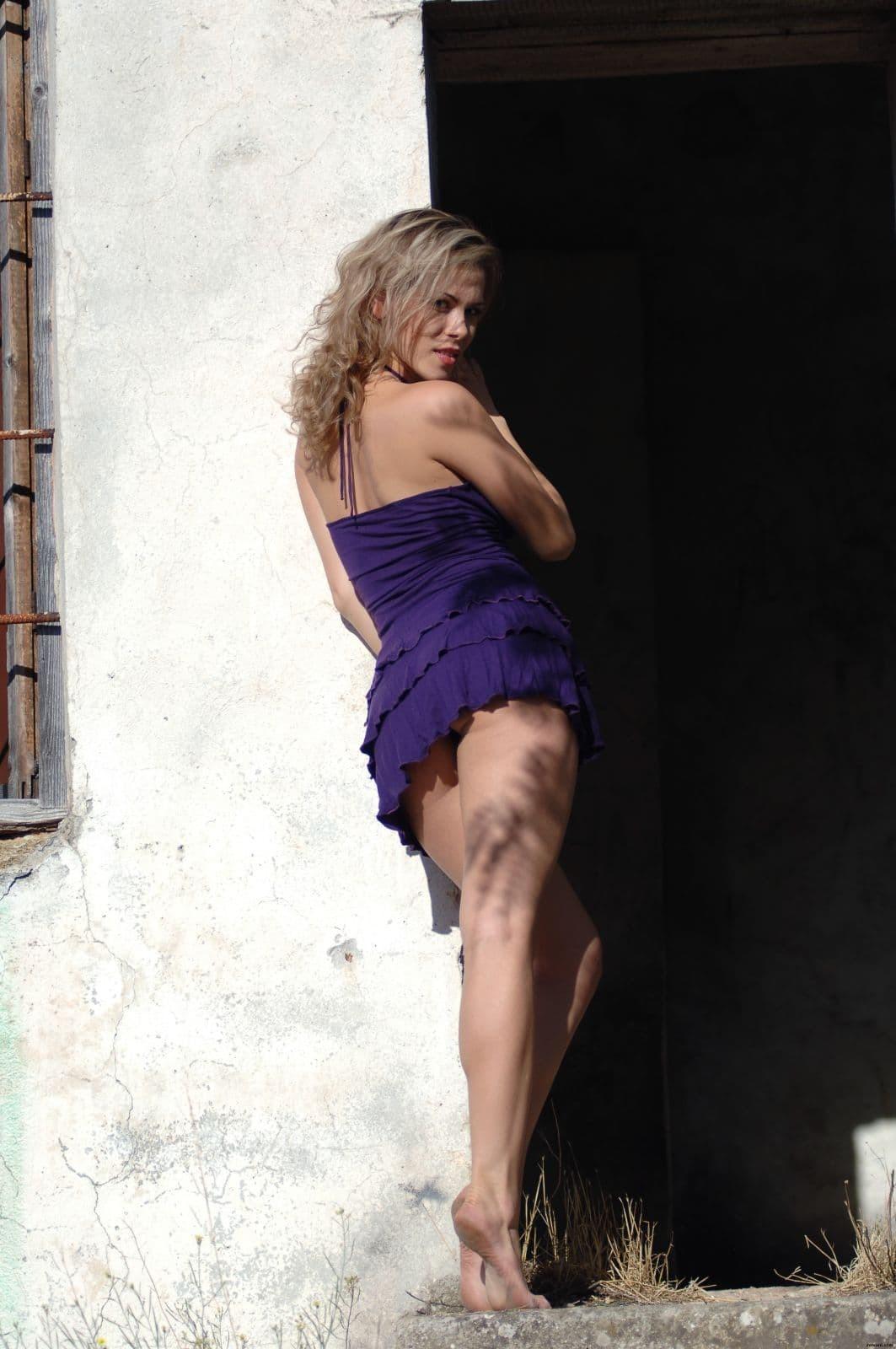 Девушка в коротком платье на крыльце - фото