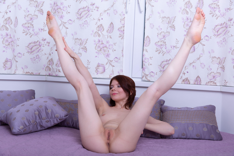 Модель раздвигает ноги на диване - фото