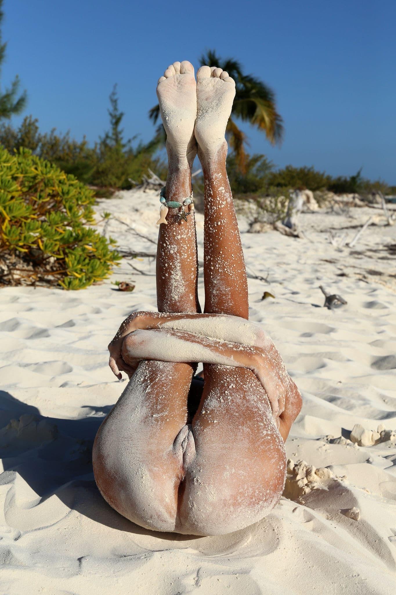 Загорелая девка в песке без купальника - фото