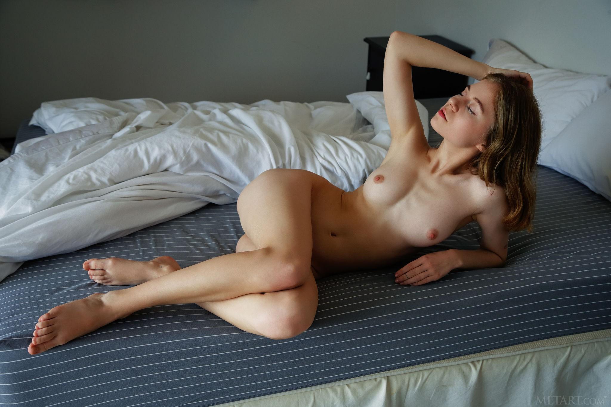 Молодая красотка разделась в постели - фото