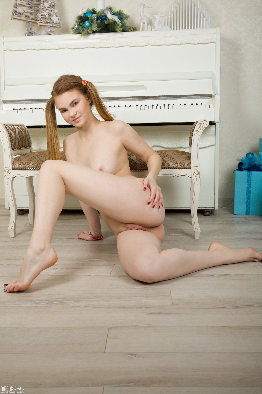 Обнажённая девушка с двумя хвостиками на полу - фото