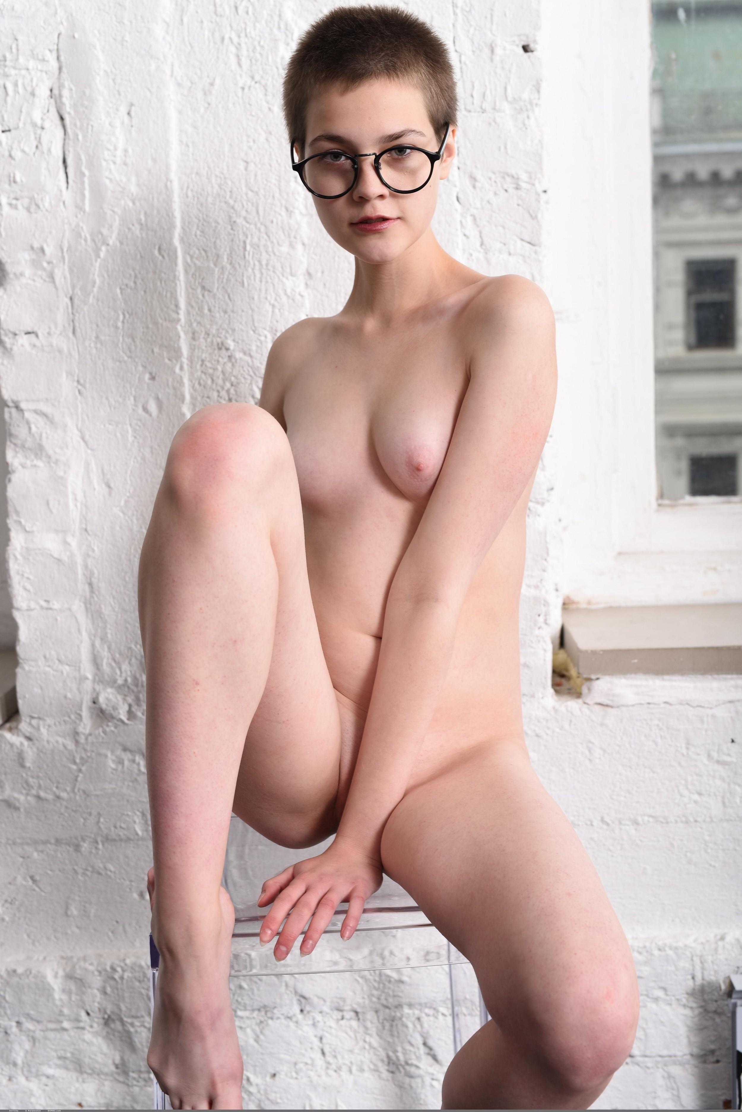 Коротко стриженная голая девушка в очках на стуле - фото