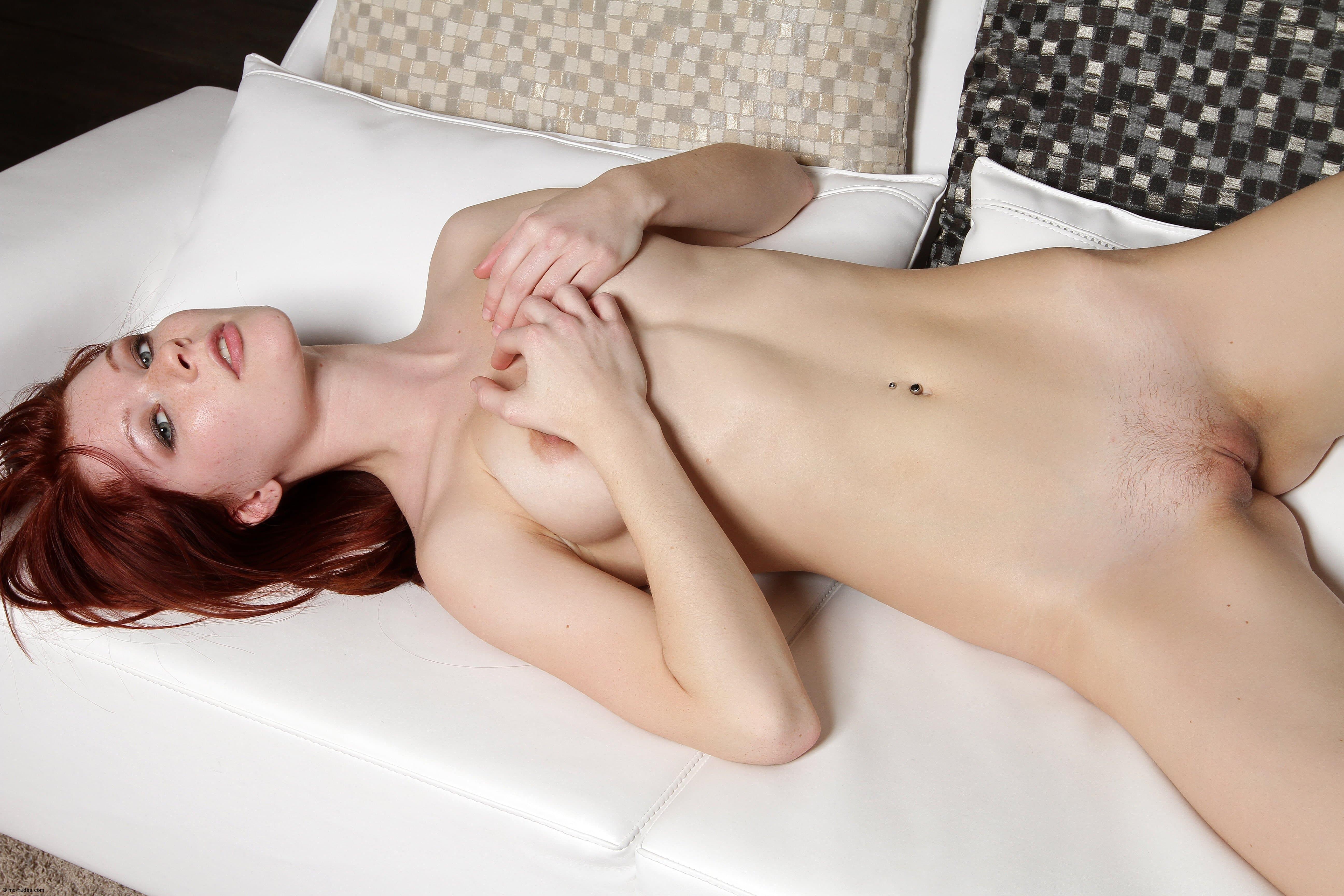 Раздетая рыжая девушка с татуировкой на спине - фото