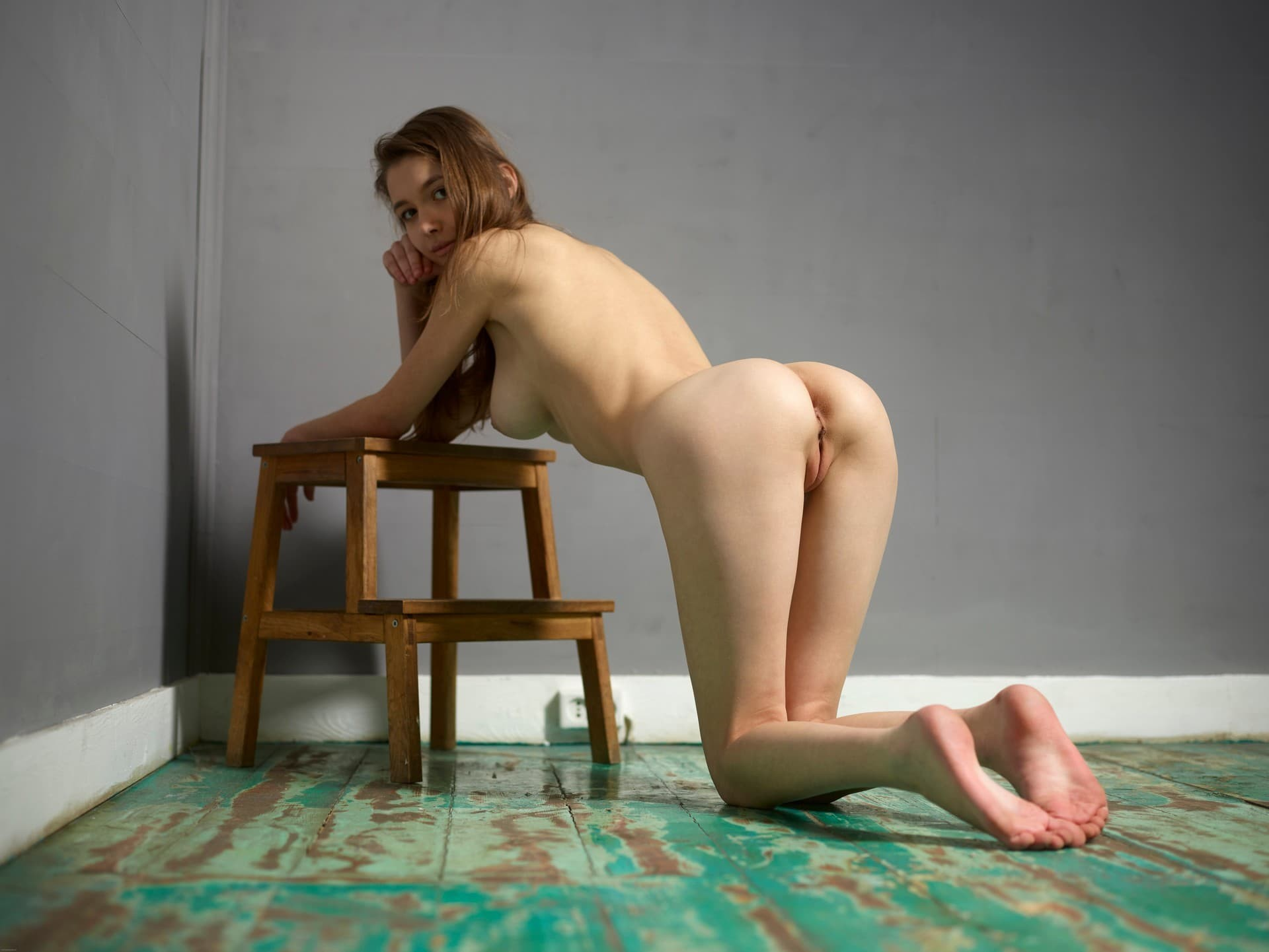 Голая девушка на коленках на полу - фото