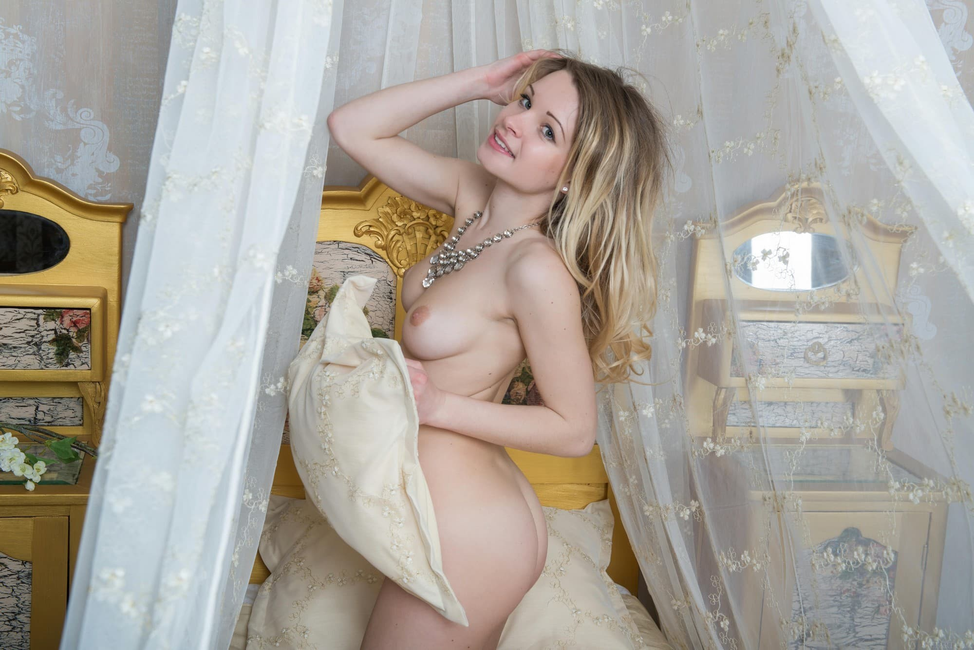 Сексапильная девица без одежды позирует на кровати - фото