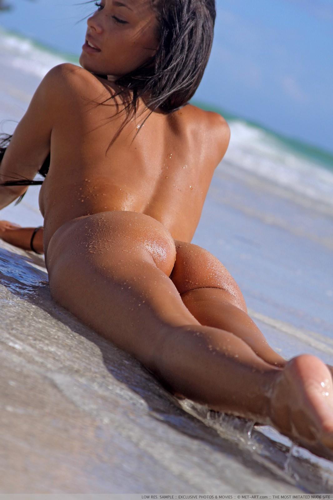 Загорелая брюнетка в масле на пляже - фото