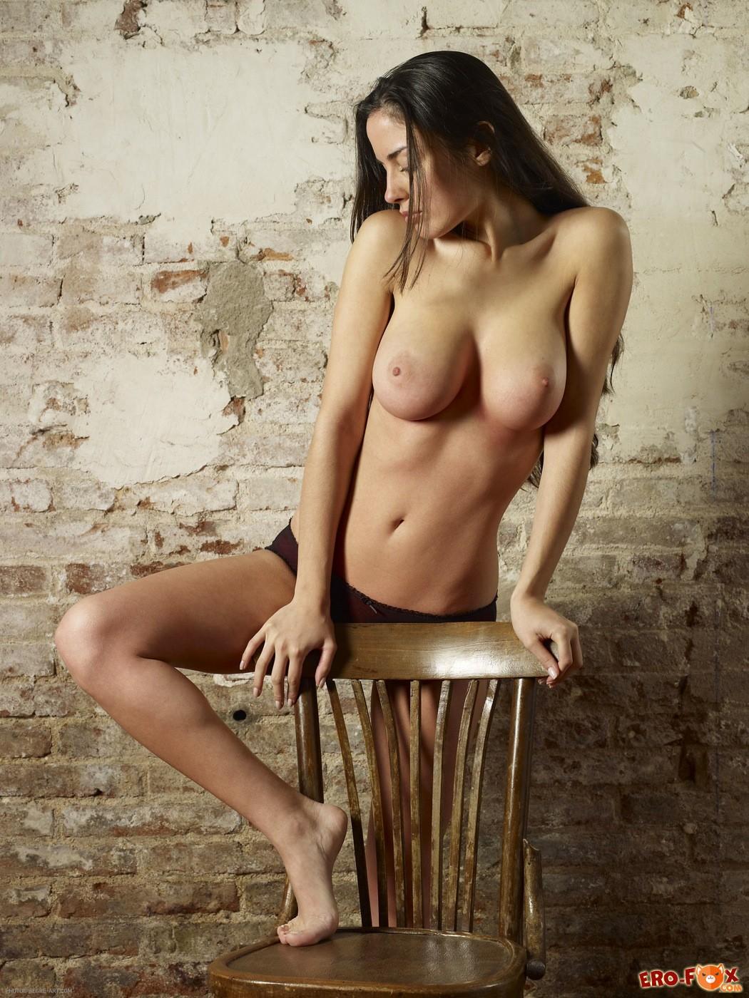 Девушка с большими сиськами на стуле - фото