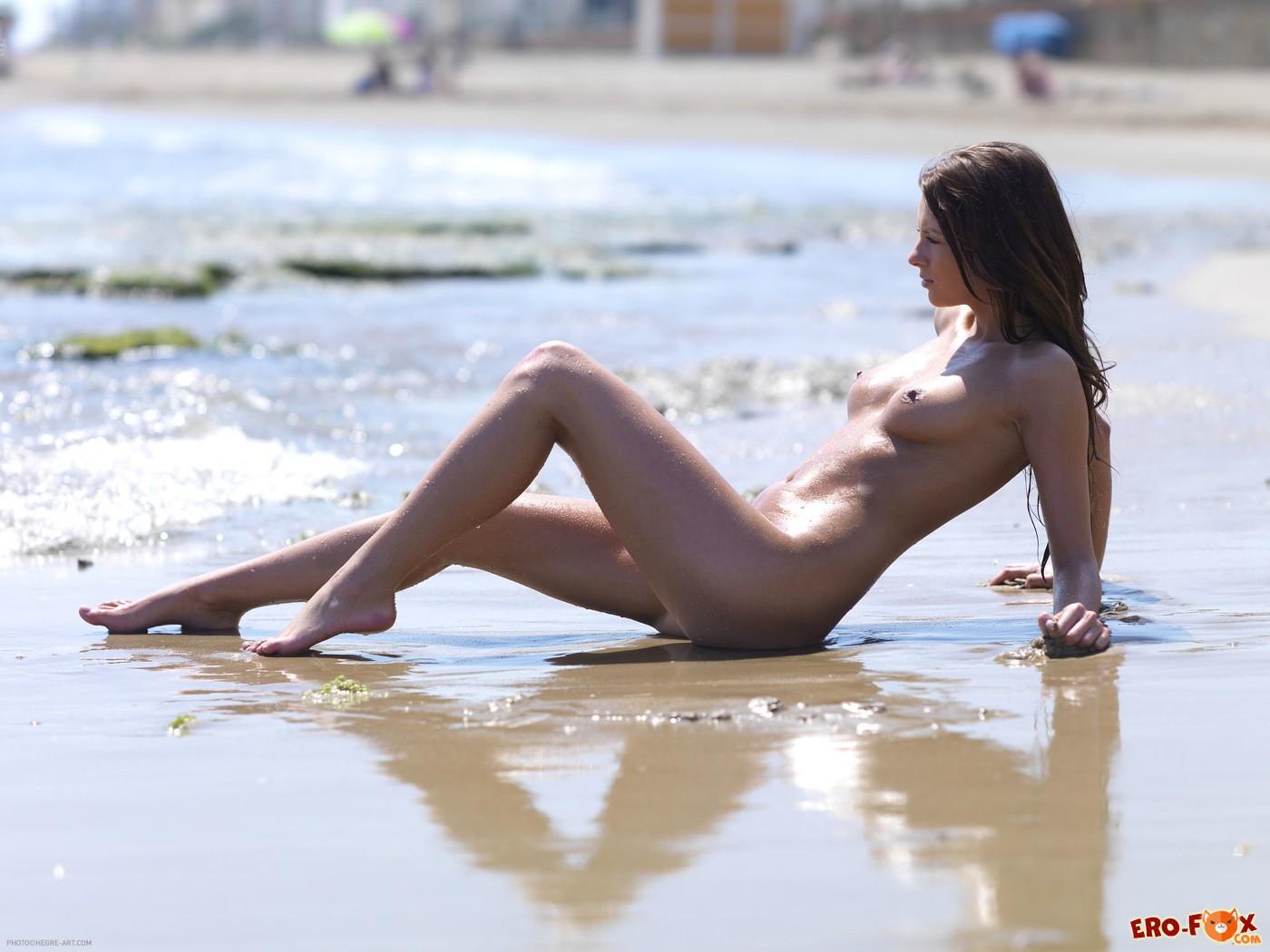 Голенькая нудистка купается на пляже - фото