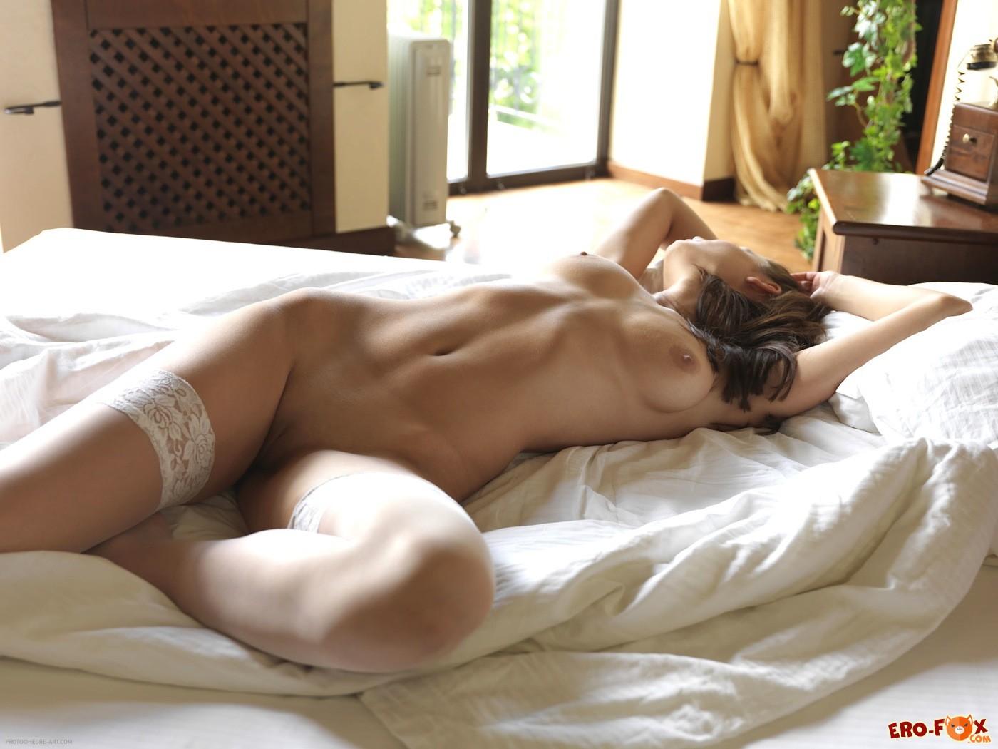 Девушка с голыми ягодицами в чулках на кровати - фото