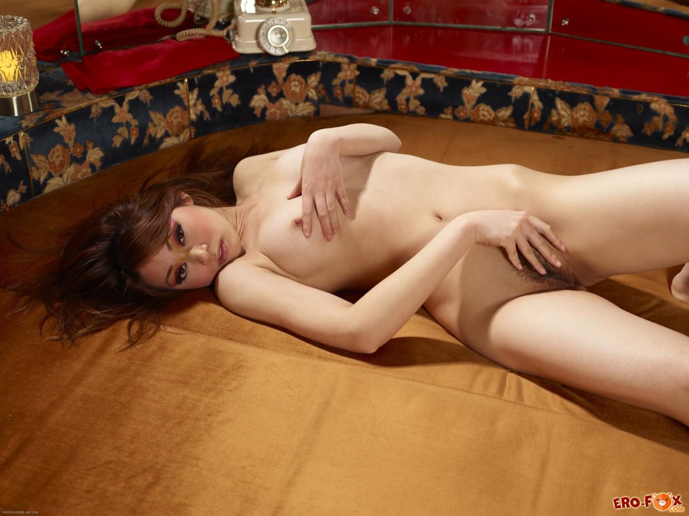 Азиатка с упругой грудью стягивает трусики на кровати - фото