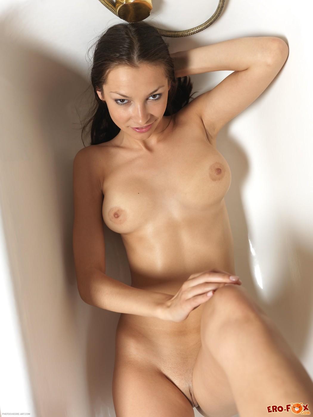 Сексапильная голая девушка в пустой ванне - фото