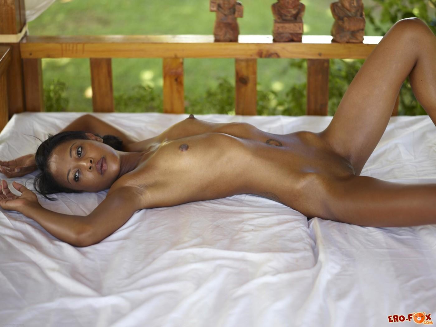 Голая худая негритянка с плоскими сиськами в постели - фото