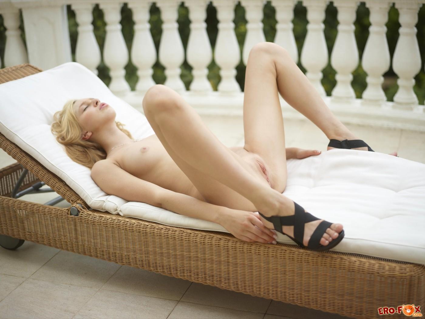 Красивая блондинка раздвинула ноги лежа на шезлонге - фото