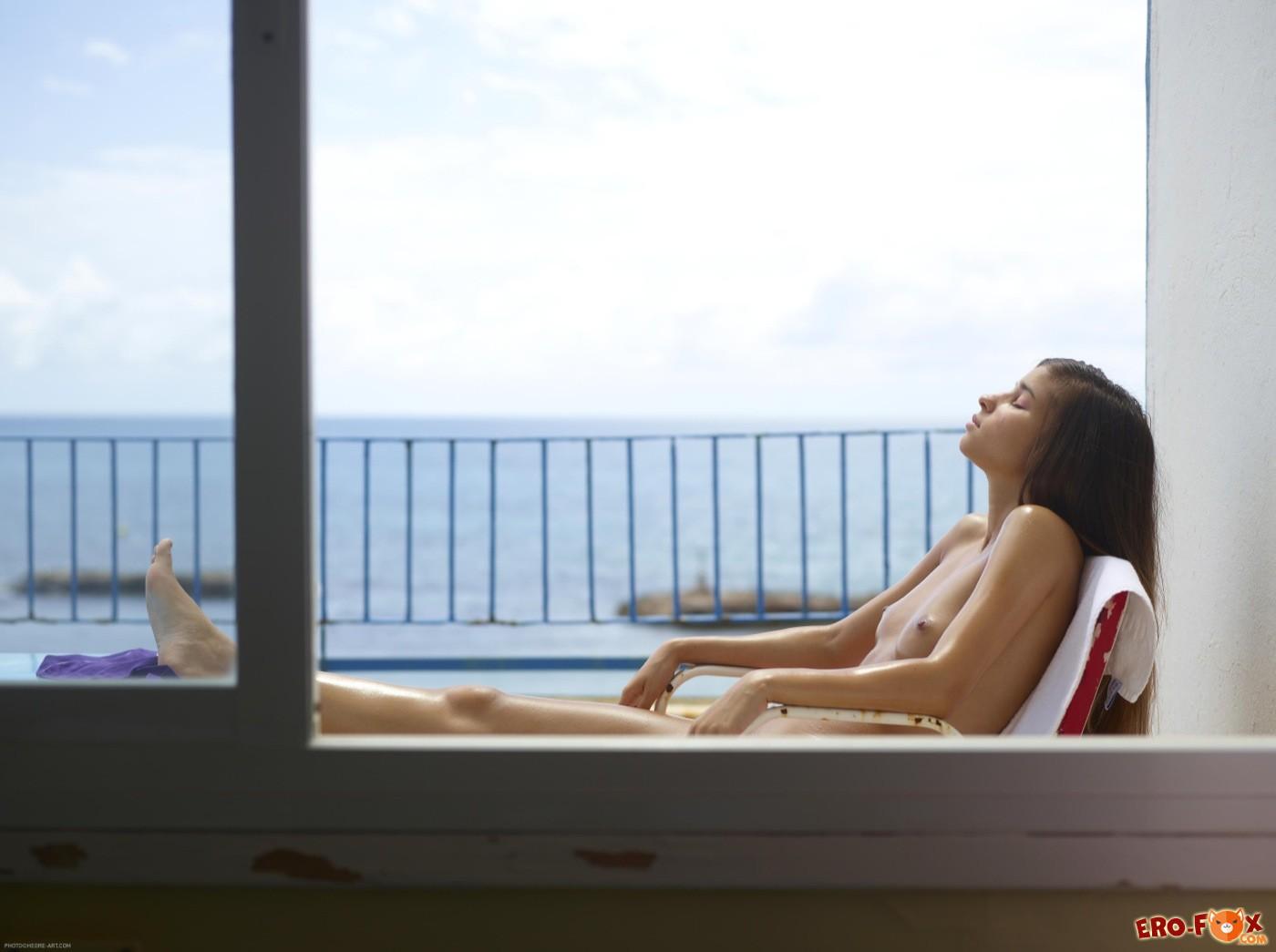 Намазанная маслом голая девка загорает на балконе - фото