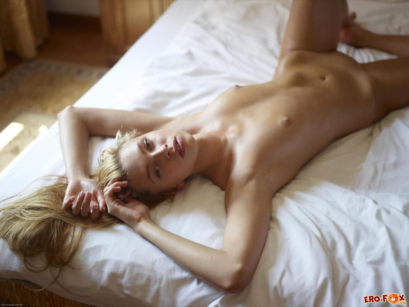 Блондинка с аппетитной щёлкой лежит на кровати - фото