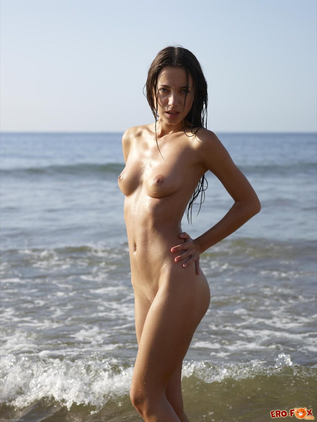 Худая брюнетка голая купается в море среди нудистов - фото