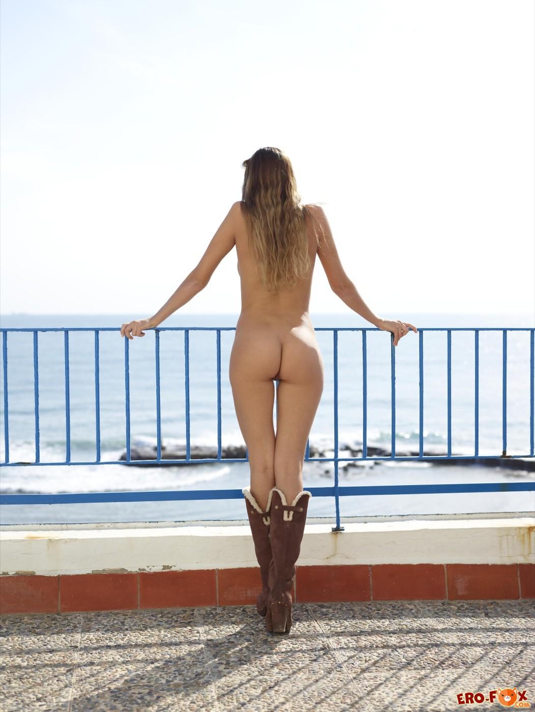 Голая русская девушка в сапогах позирует на курорте - фото