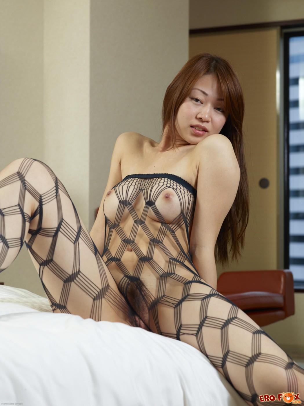 Развратная азиатка в сетчатом комбинезоне на кровати - фото