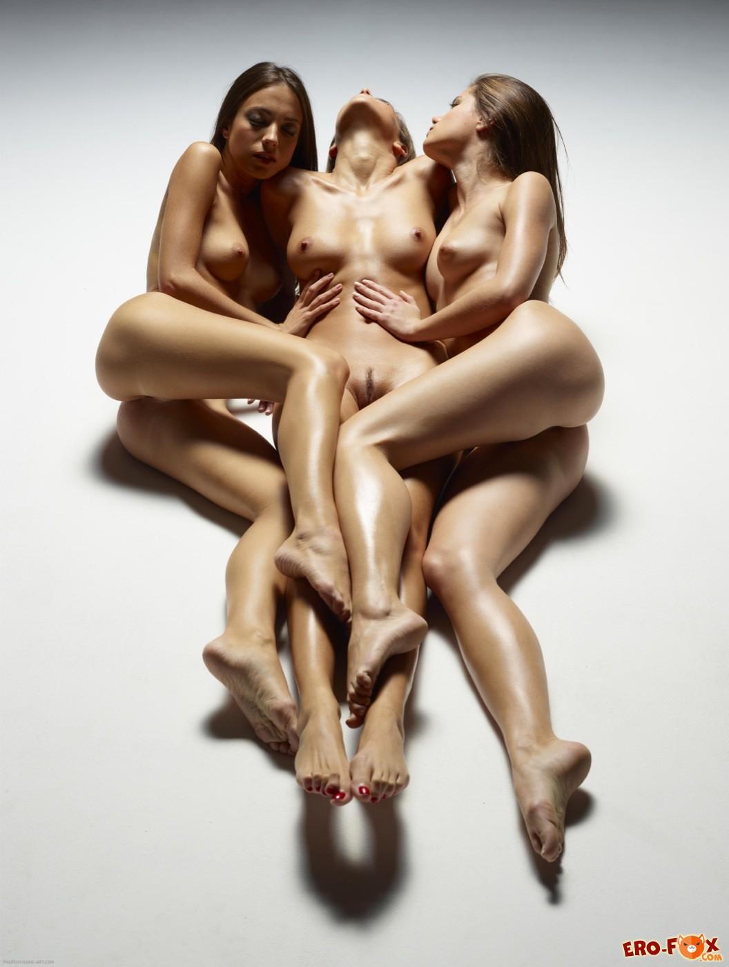 Три голые девушки лежат на полу в обнимку - фото
