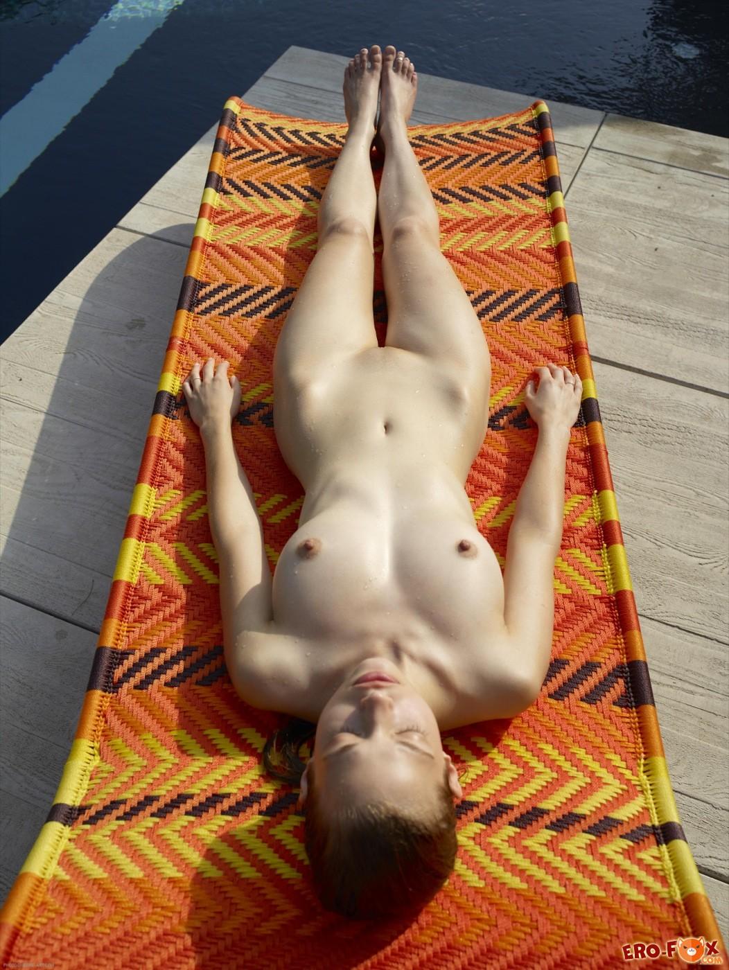 Мокрая девушка голая загорает на шезлонге - фото