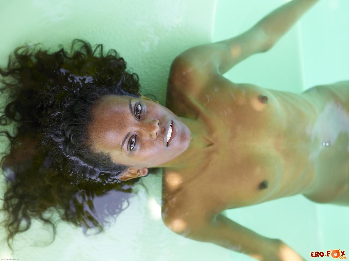 Тощая негритянка голая купается в бассейне - фото