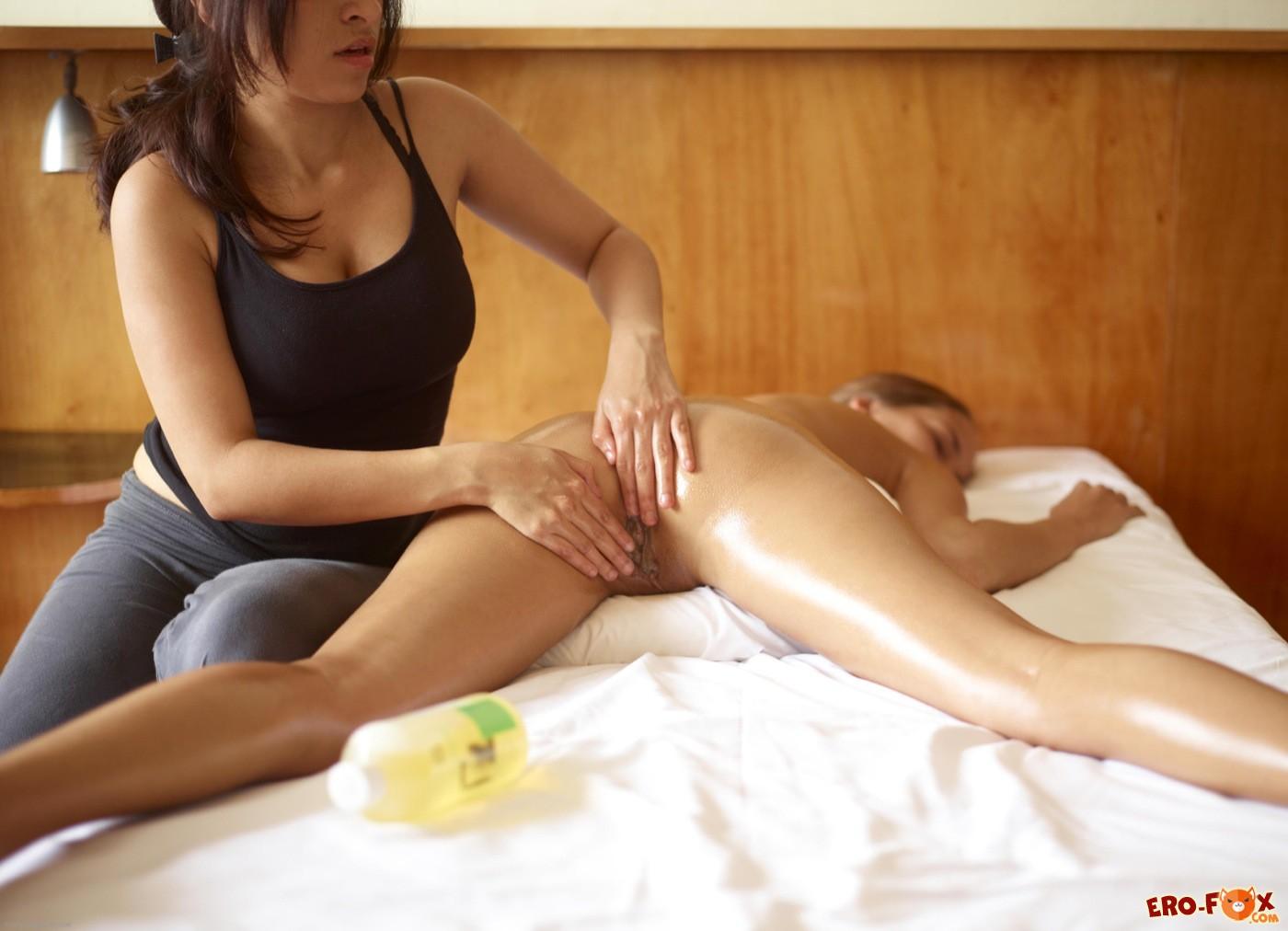 Голой девушке в масле делают массаж на кровати - фото