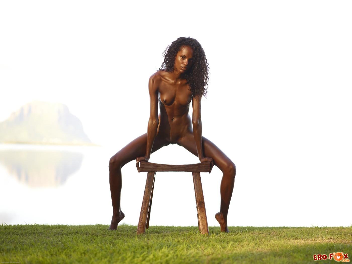 Худая негритянка голая на табуретке - фото