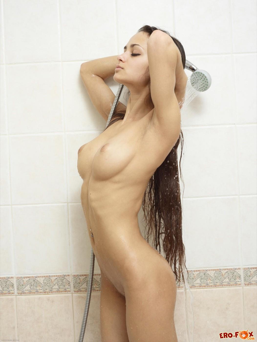 Голая красавица обливается водой  - фото