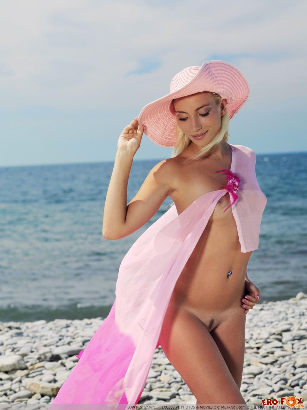 Голая девица в шляпке эротично позирует на пляже - фото