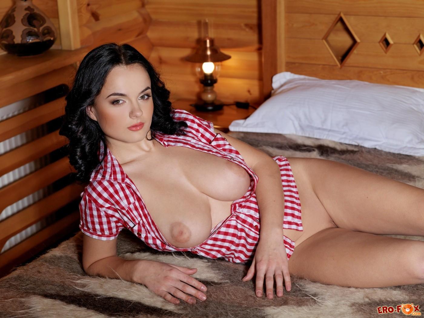 Брюнетка с крупной грудью в рубашке на кровати - фото