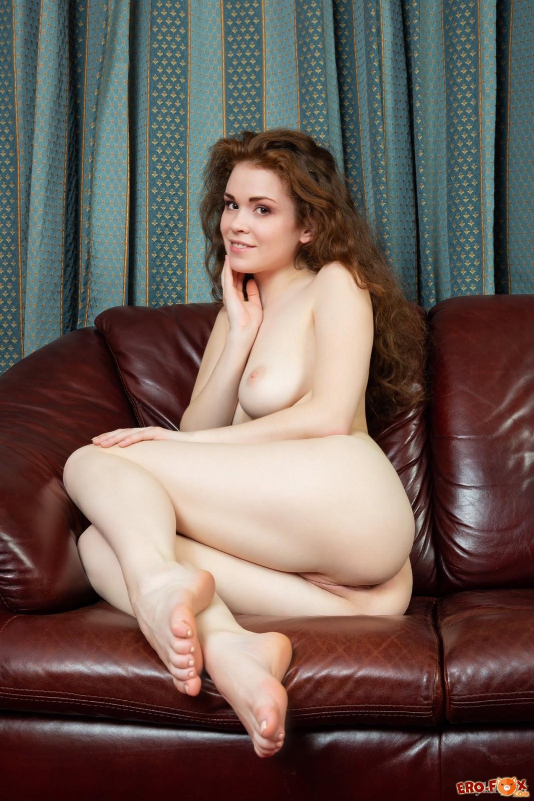 Сексуальная девушка снимает черные трусики на диване - фото